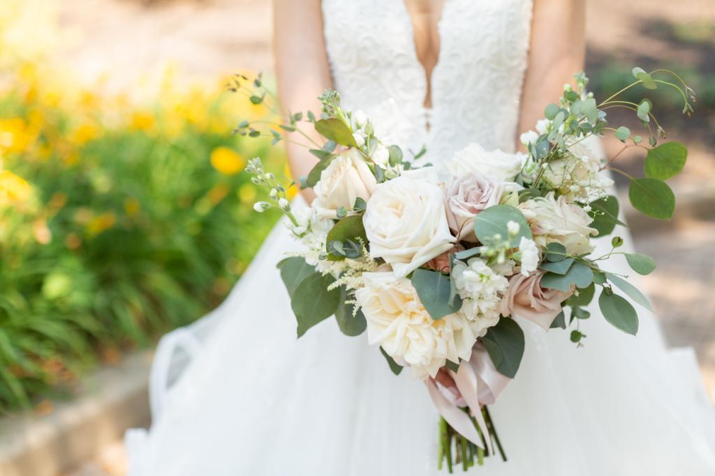 Bride holding white and light pink wedding bouquet