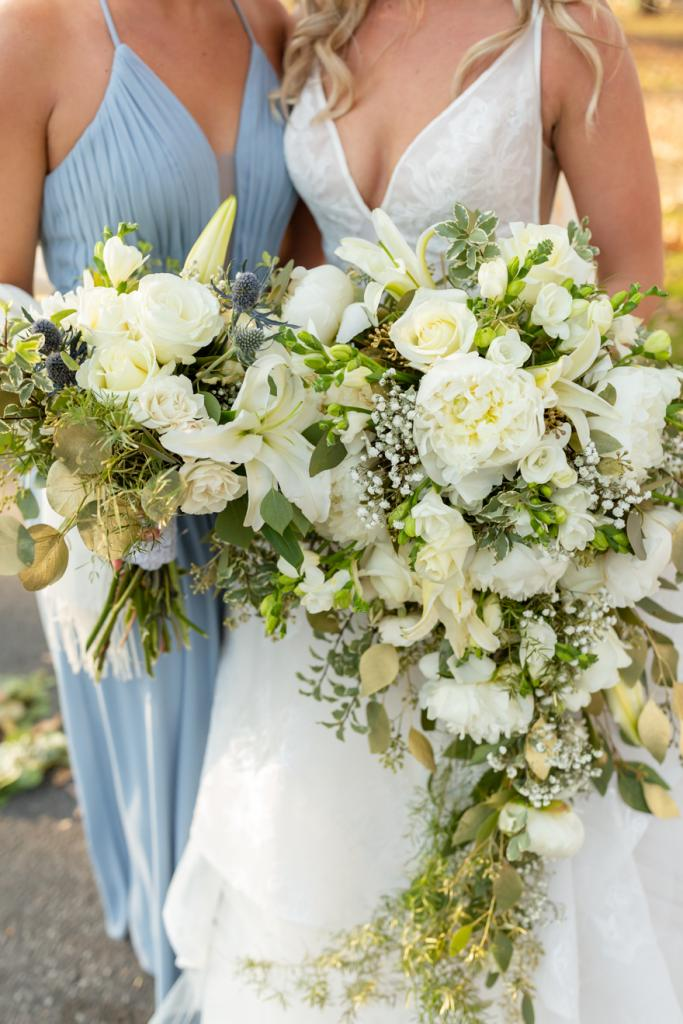 Bride and bridesmaid holding white wedding bouquet