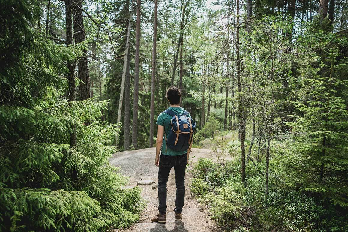 Man standing in Megève forest looking at the trees