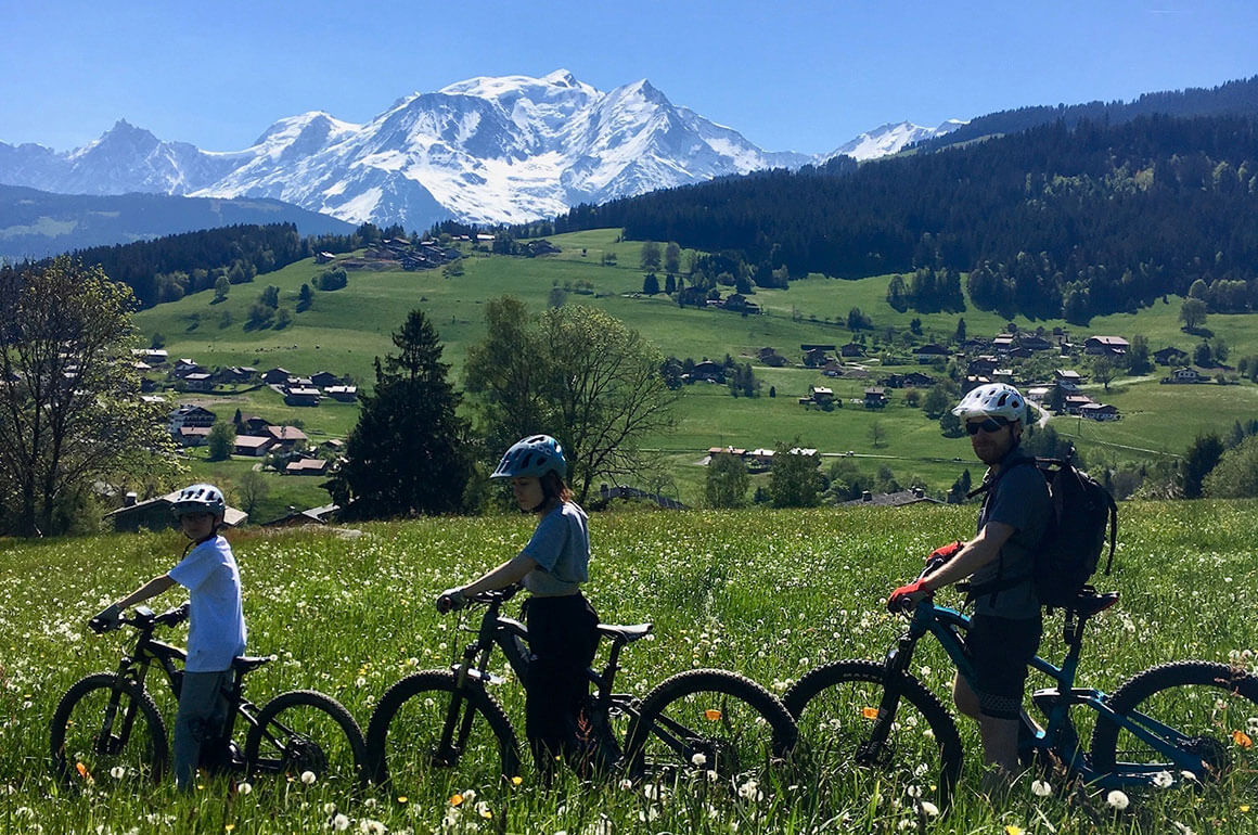 Family crossing a sunny flower field on electric mountain bikes