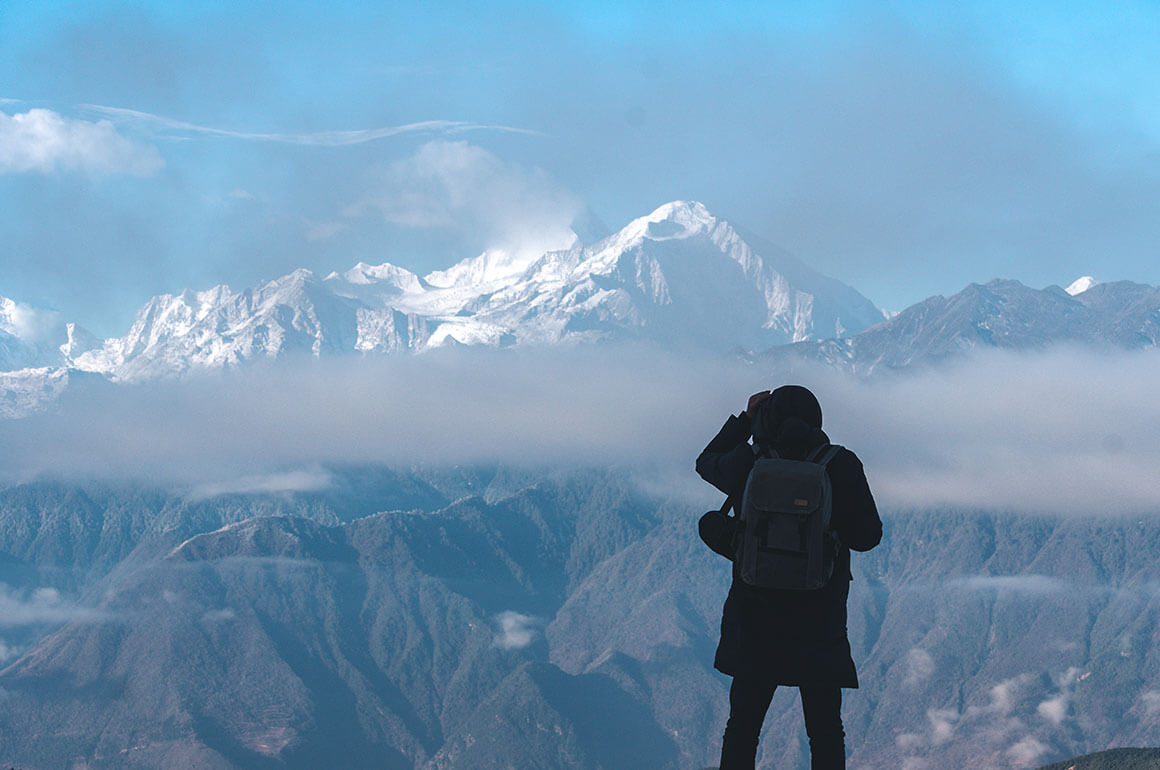 A man taking a picture of the snowy massif of Mont Blanc in front of him