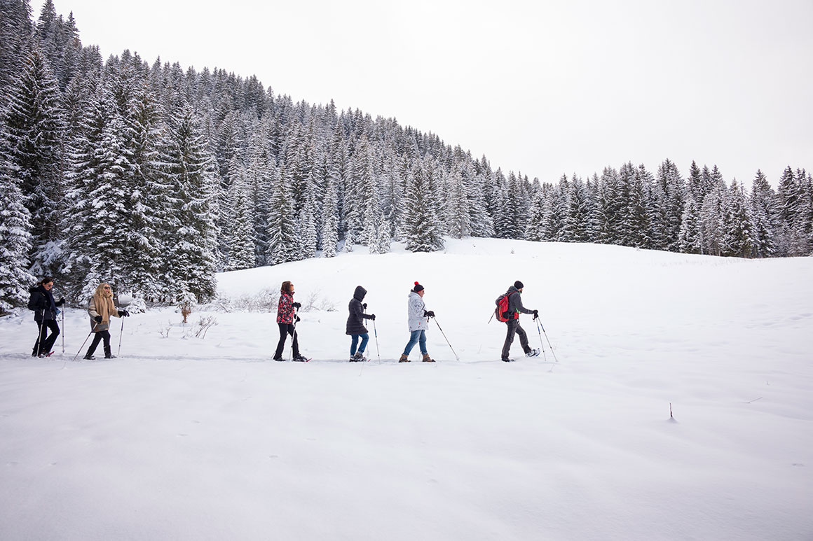 Group of hotel guests crossing a snow field with snowshoes near Megeve