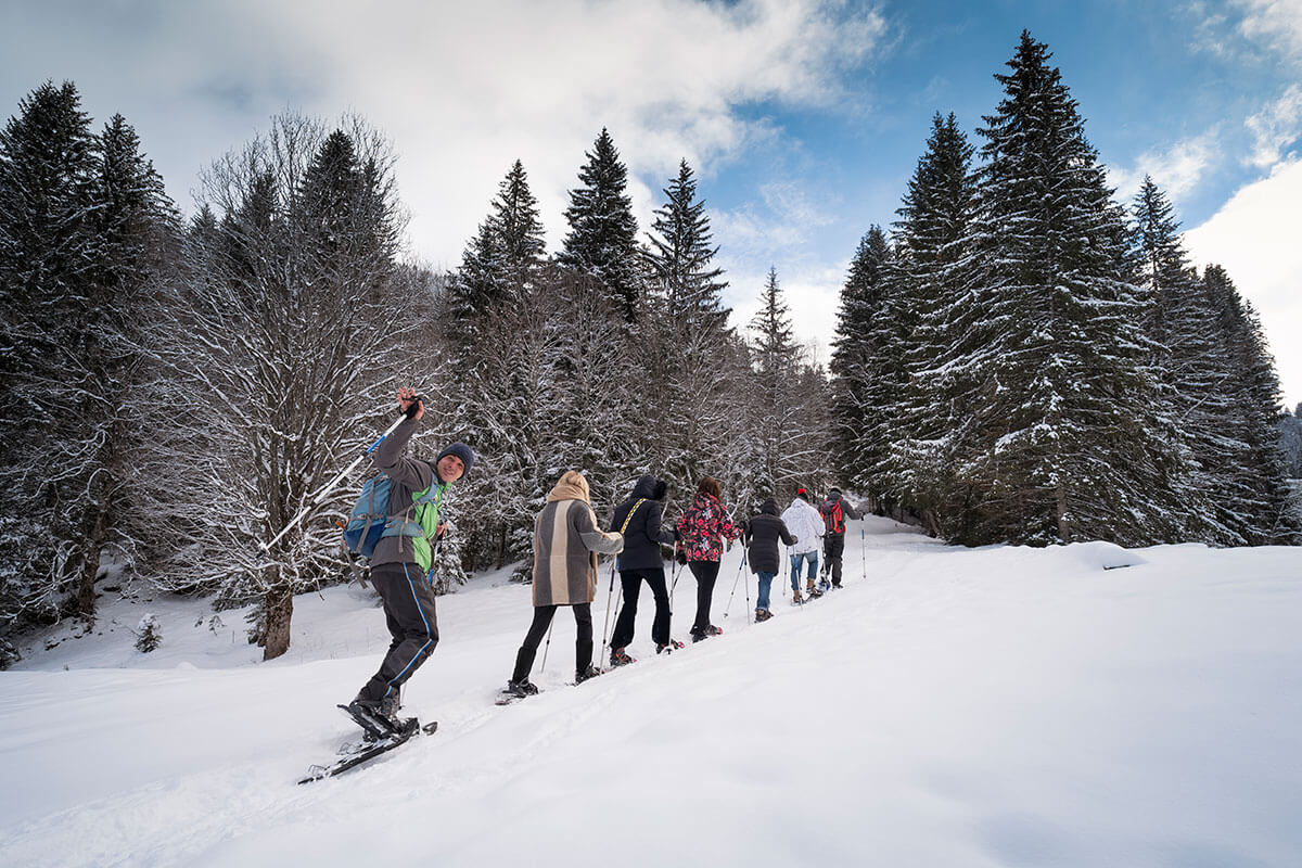 Groupe traversant un champ enneigé en raquettes près de Megève