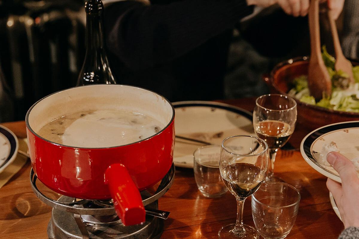 Clients du Coeur de Megève mangeant de la fondue et buvant du vin au refuge du Tornieux