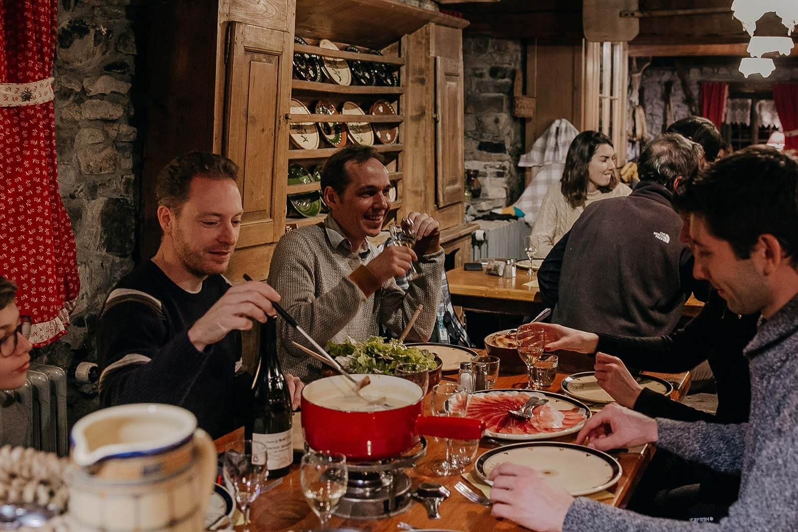 Coeur de Megève guests eating fondue and drinking wine at refuge du Tornieux