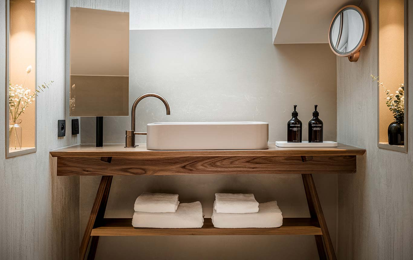 Family Suite - bathroom with copper basin and faucet, bathrobes in the lower part, light coming from the canopy