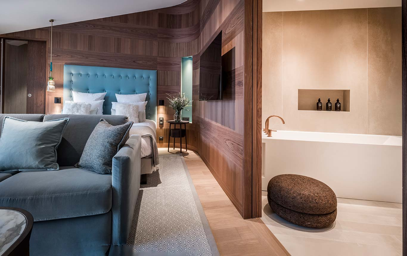 Suite - bathtub with cork footstool on one side, bed with blue sofa on the other side