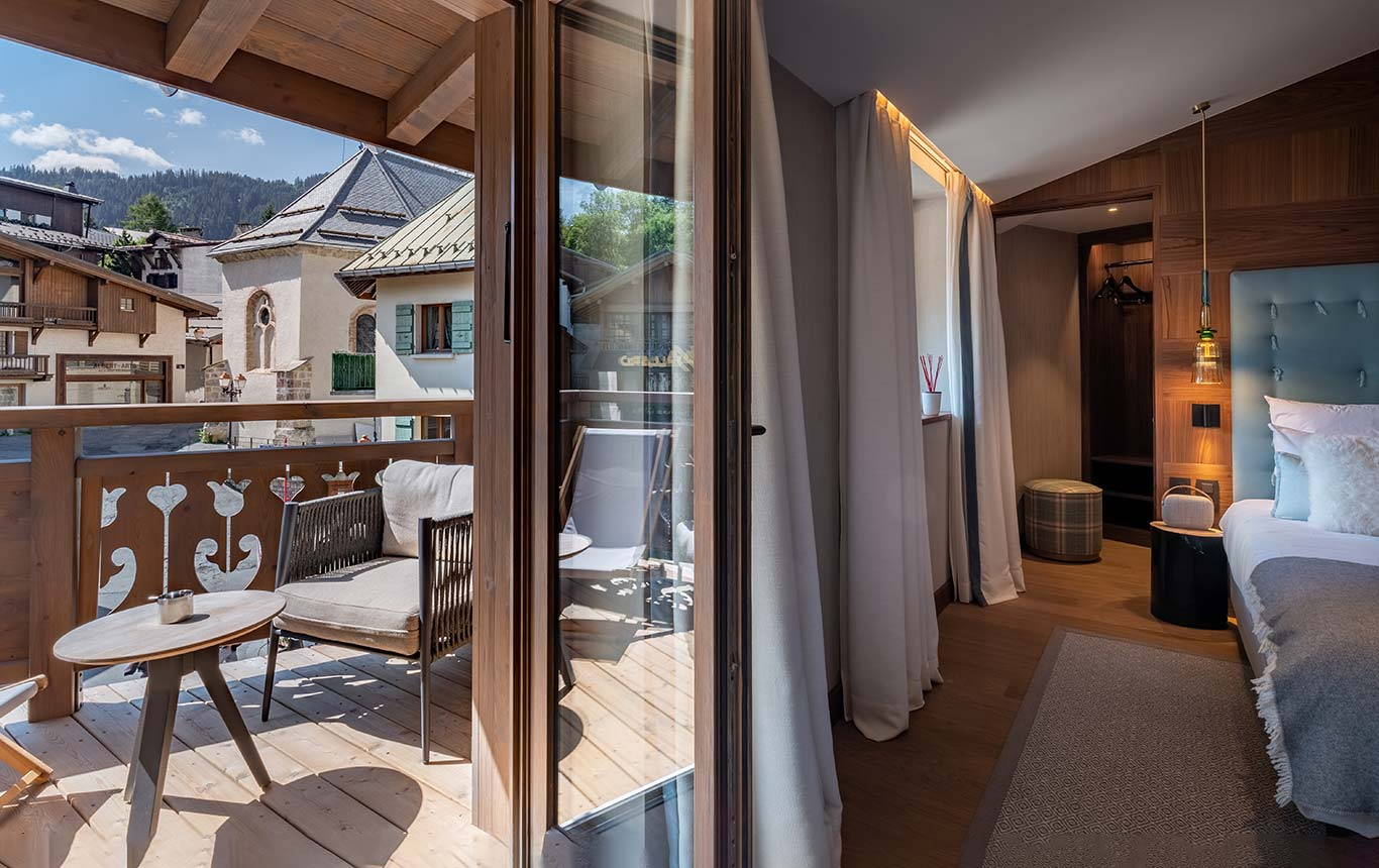 Suite - view on the sunny balcony with sun lounger, coffee table and view of the village