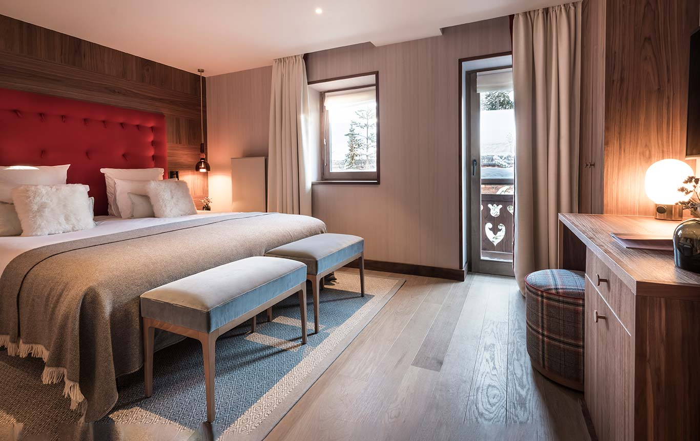 Superior Room - wooden desk area, bed with brick coloured headboard and balcony overlooking the village of Megeve