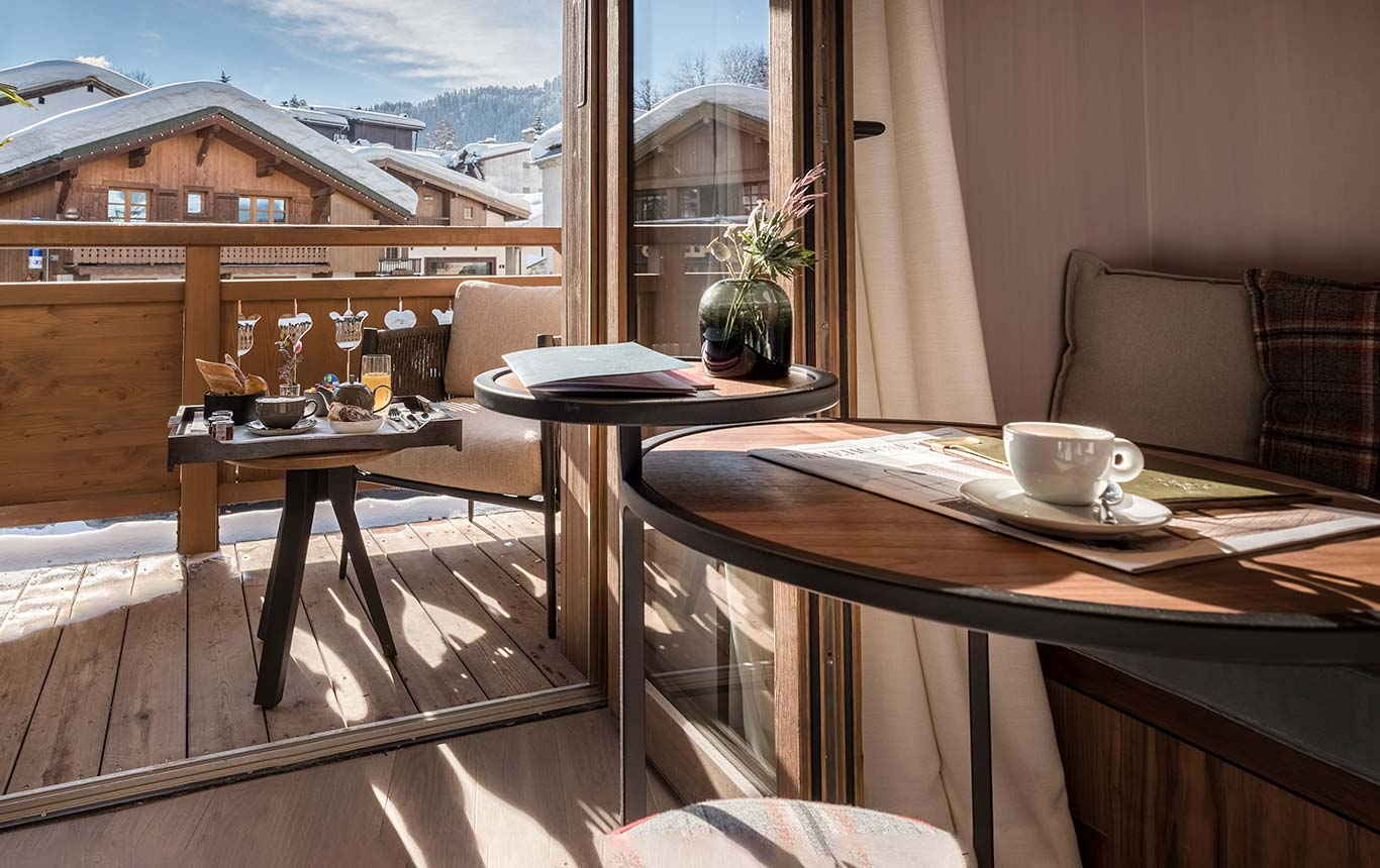 Superior Room - sunny terrace overlooking the snowy roofs of Megeve