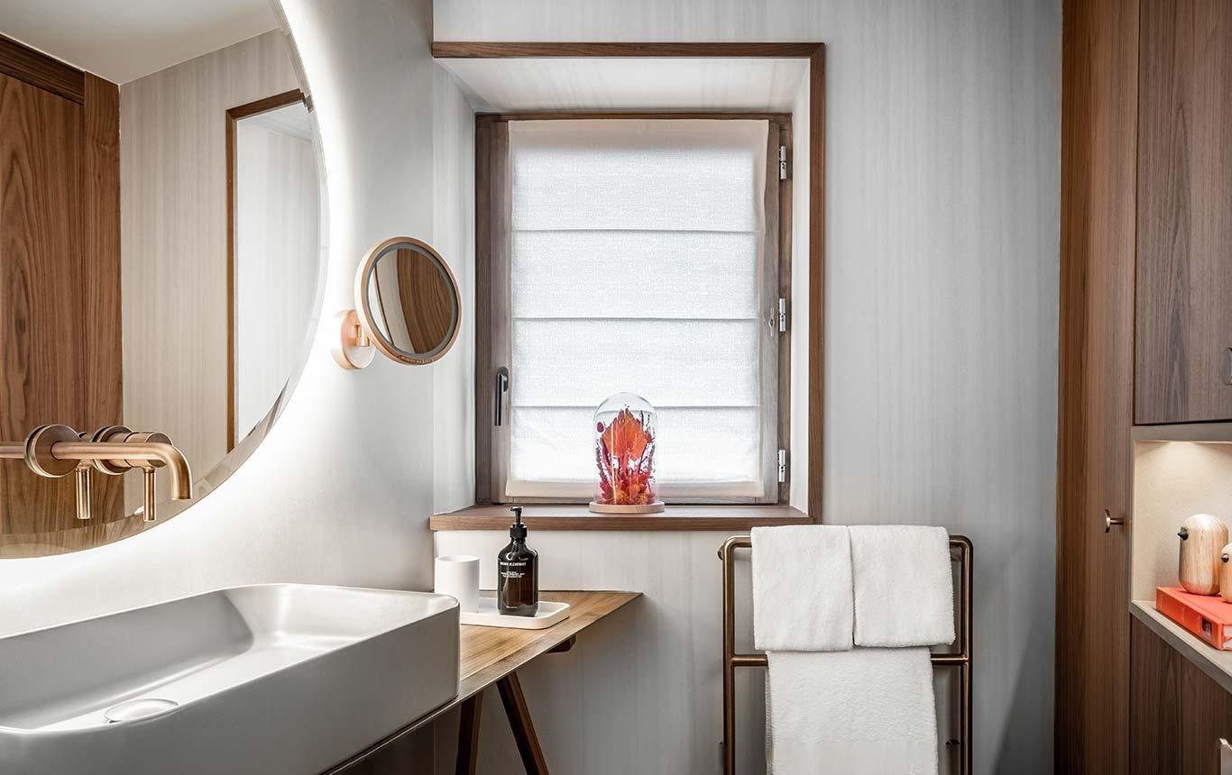 Superior Room - Semi-open bathroom with stone basin and large round backlit mirror