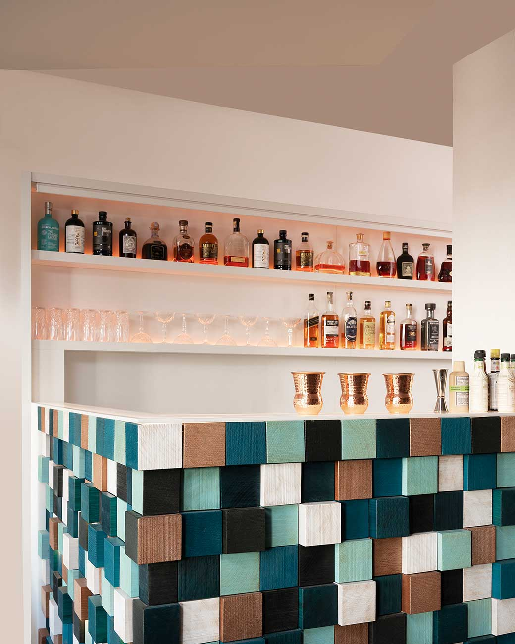 View of the cocktail bar in coloured wooden squares, shelves with alcohol bottles