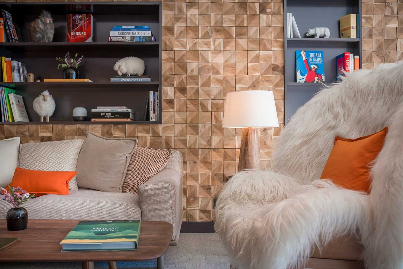 Sofa and armchair in faux fur, bookcase and wall in squares of wood