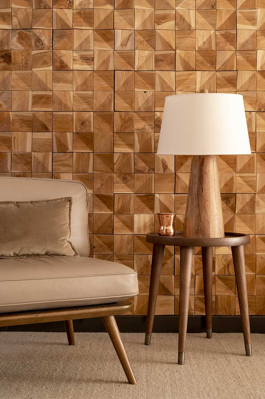 Close-up on grey leather armchair, lamp with lampshade and wall in wooden squares