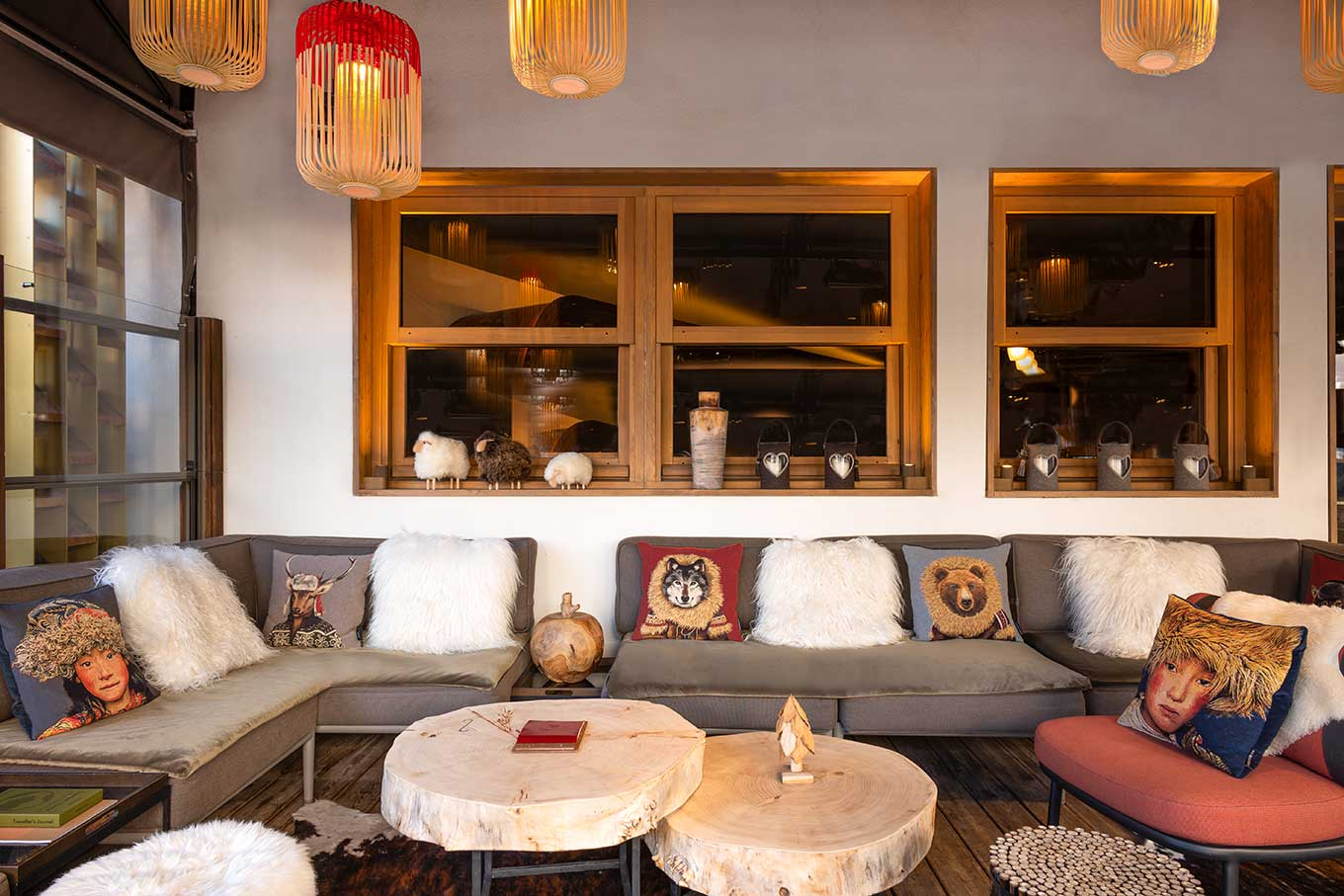 Covered terrace with faux animal skins, cushions, wooden coffee tables and braziers