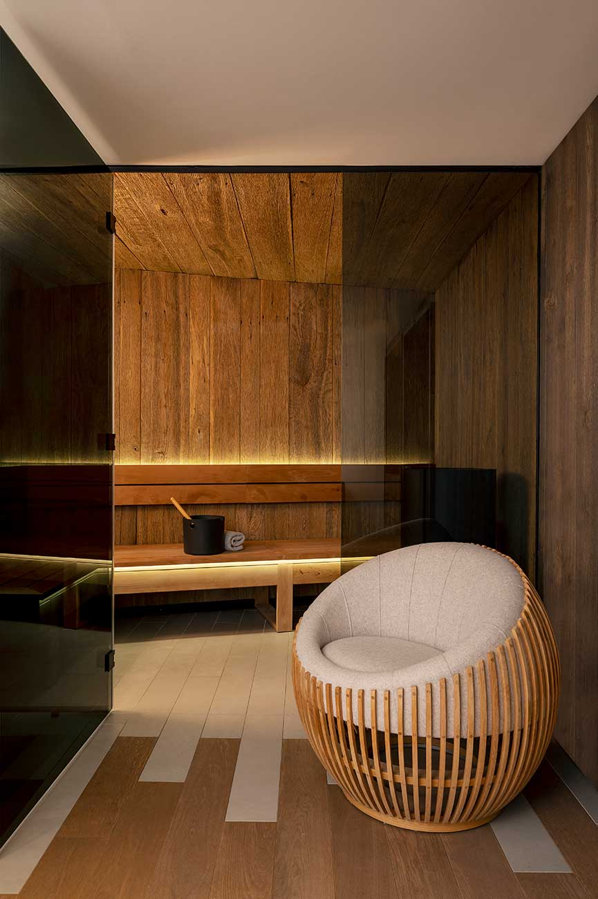 Sauna seen from the resting area, deep armchair in wood and beige fabric