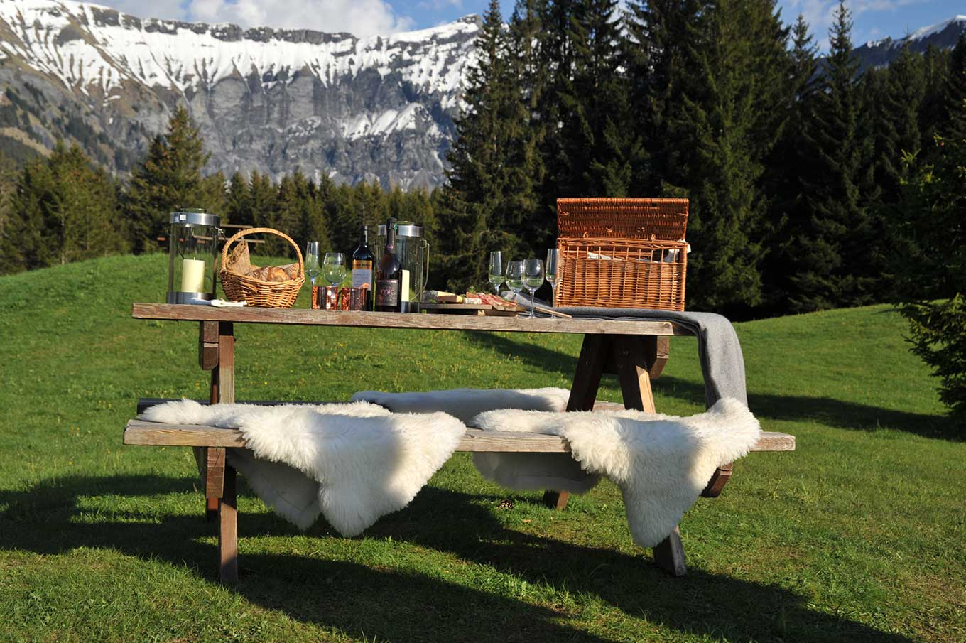 Picnic table with wooden bench and fake furs, view of the sunny mountains