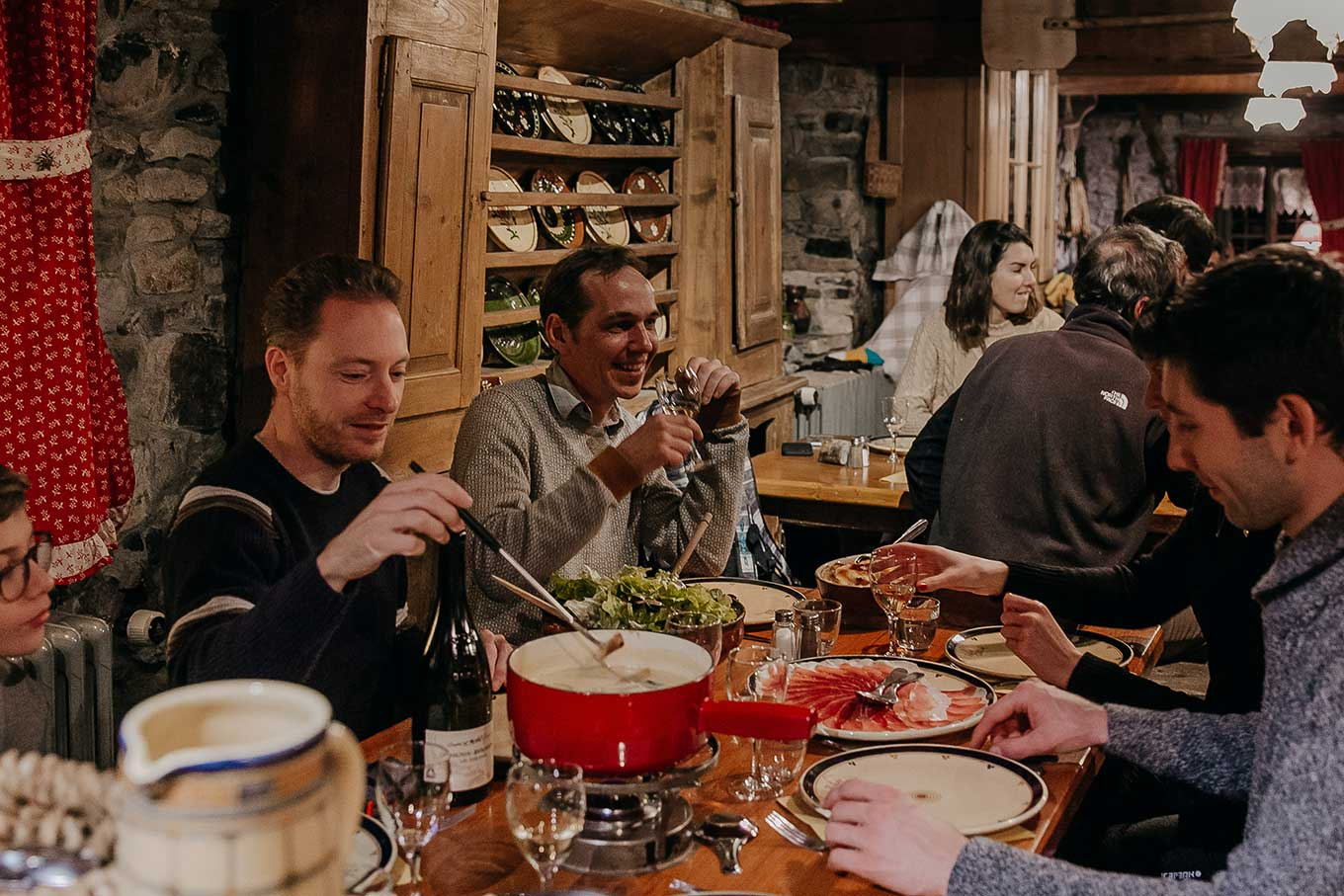 Group of friends sharing a dinner around a Savoyard fondue and white wine