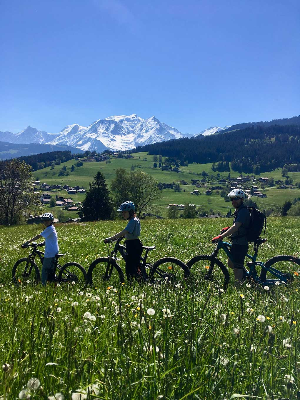 Family on electric mountain bikes in the middle of a field of yellow flowers