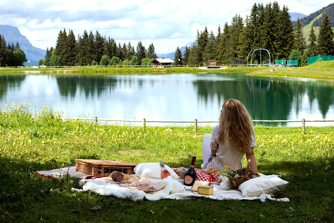 Wooden table with a picnic box, faux fur on the benches and view of the mountains