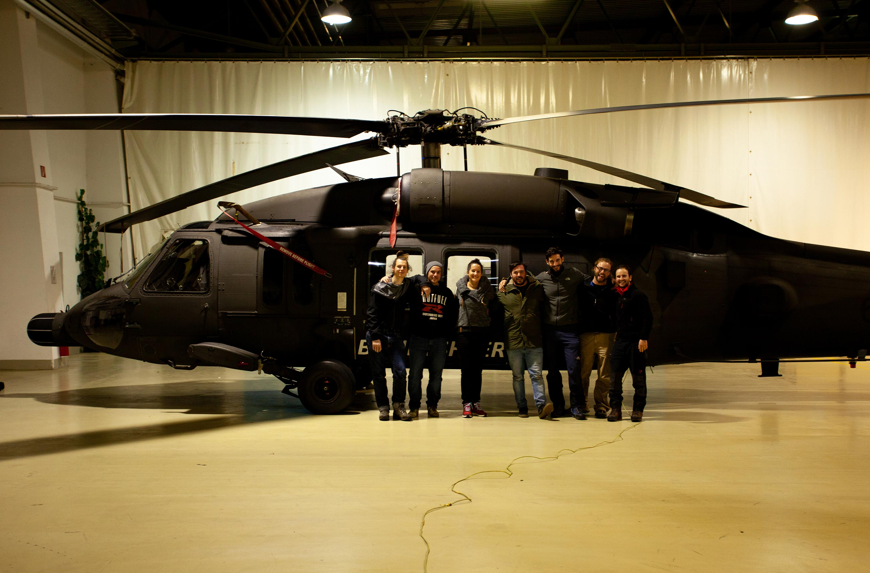 The whole 360 video production crew posing for a picture in front of a Black Hawk helicopter inside a hangar.