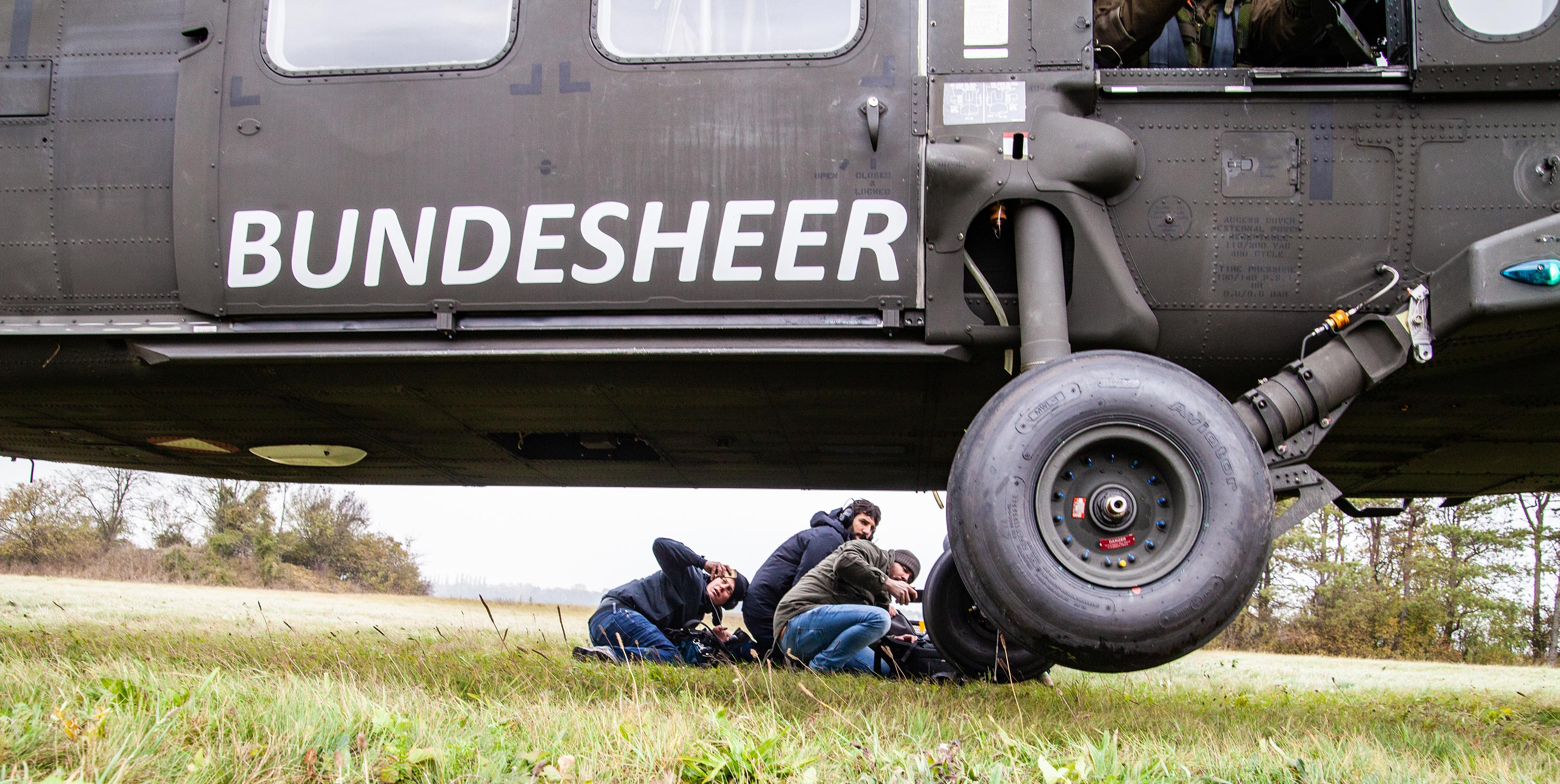 360 video film crew lying down on the floor taking a picture of the liftoff of a Black Hawk helicopter.