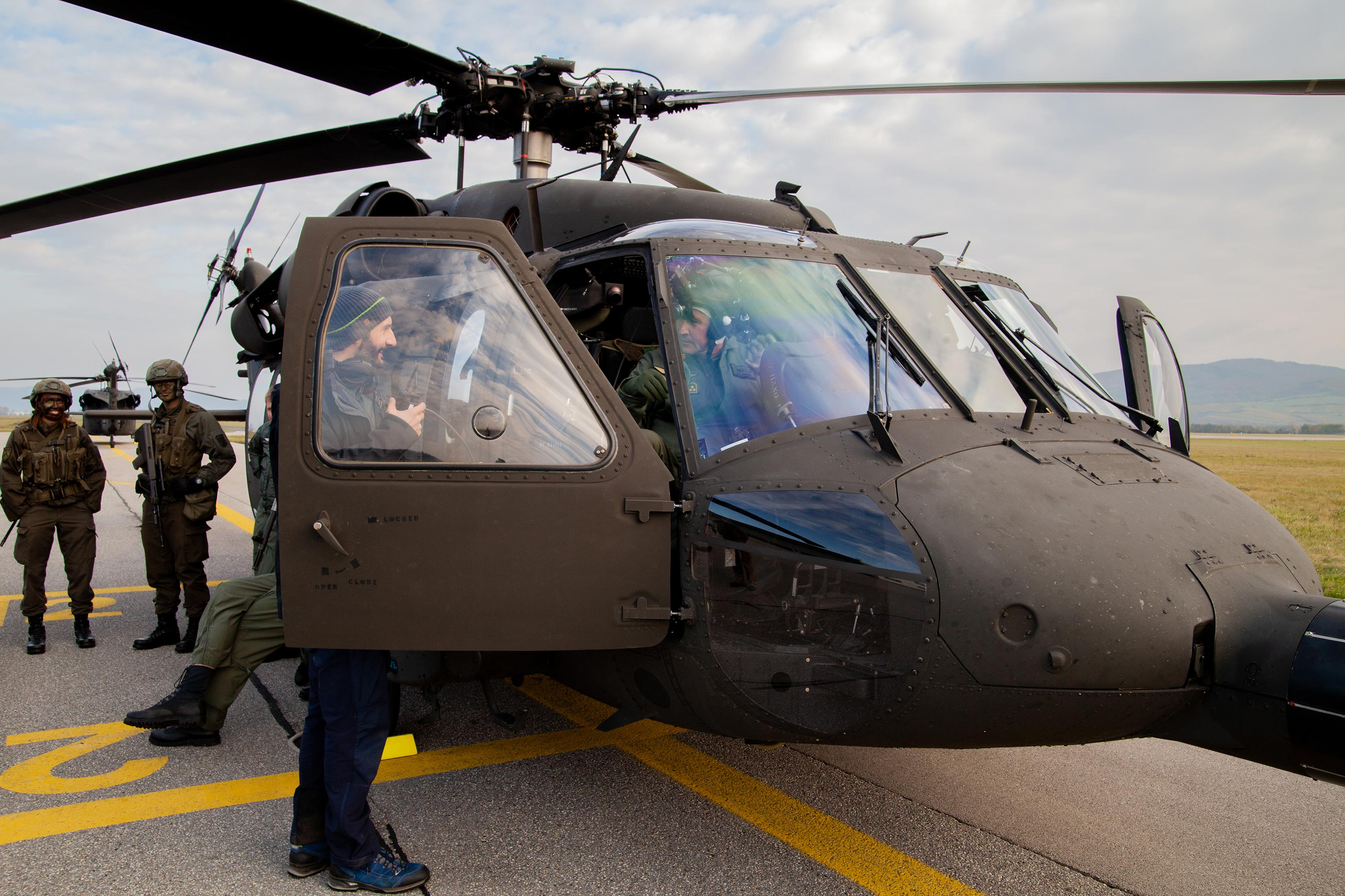 360 video director greeting a pilot sitting inside a Black Hawk military helicopter.