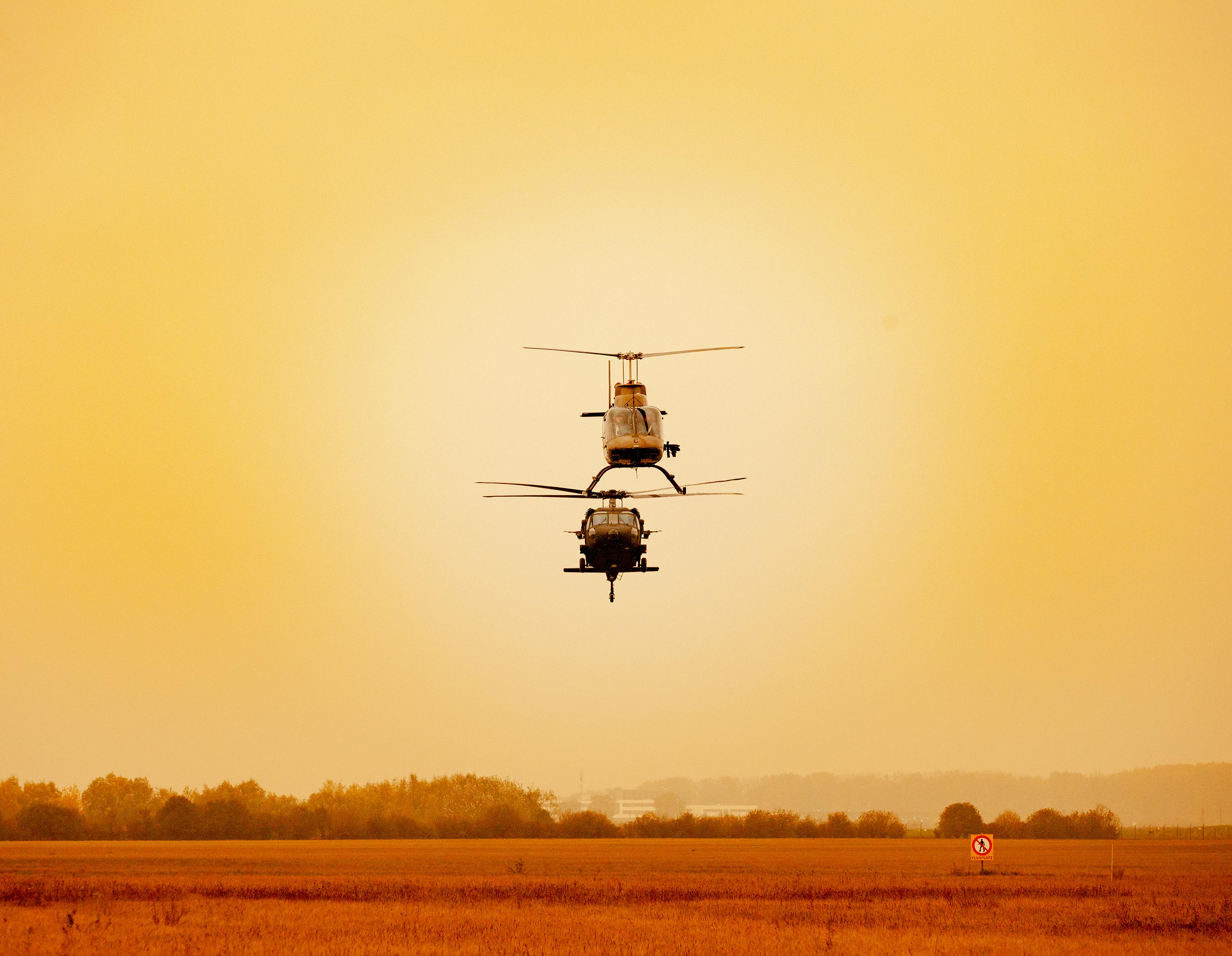 Two Black Hawk helicopters flying side by side on a sunset during a 360 video production.