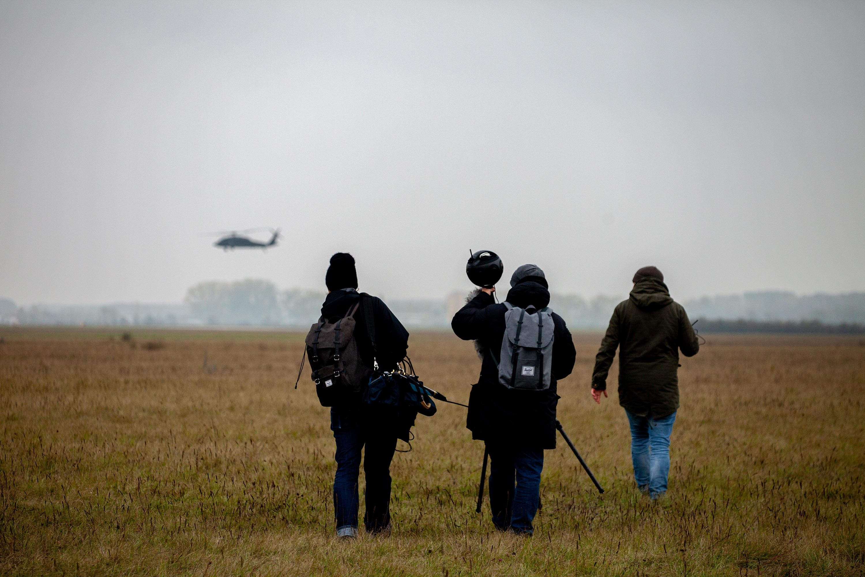 360 video film crew walking towards a Black Hawk helicopter while carrying an Insta360 Titan 360 video camera