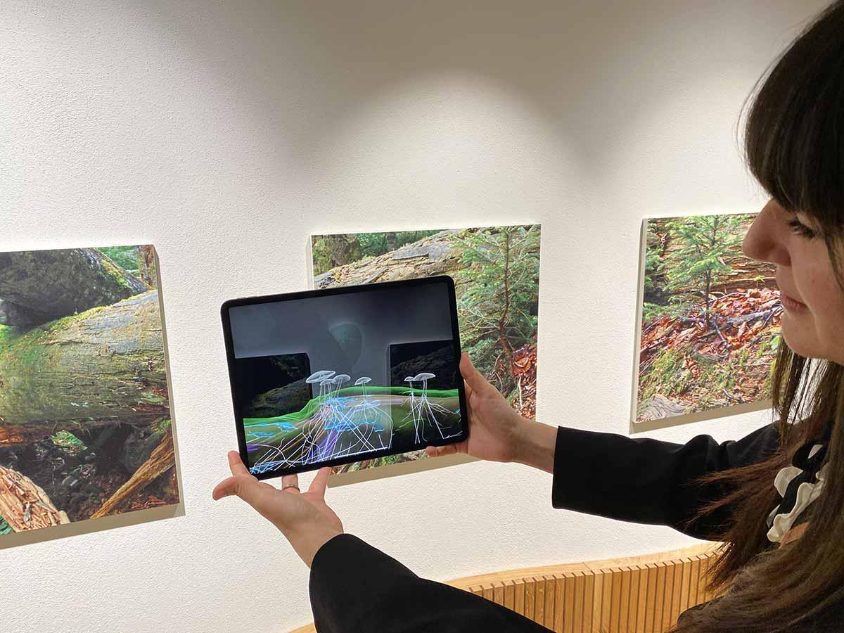 Frau hält ein iPad, das ein Augmented-Reality-Erlebnis enthält