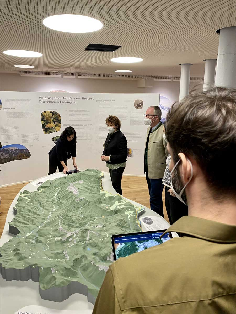 Man using an AR experience in a tablet in front of a land model