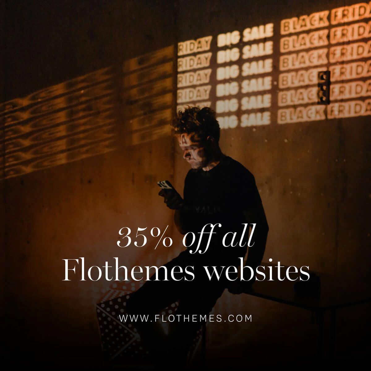 alt text for image: an image of a white man with brown hair sitting on a bench holding a phone. The words 'Big Sale Black Friday' are projected on the wall behind him. There is text overlaying the photo, which reads '35% off all Flothemes websites. www.flothemes.com'.
