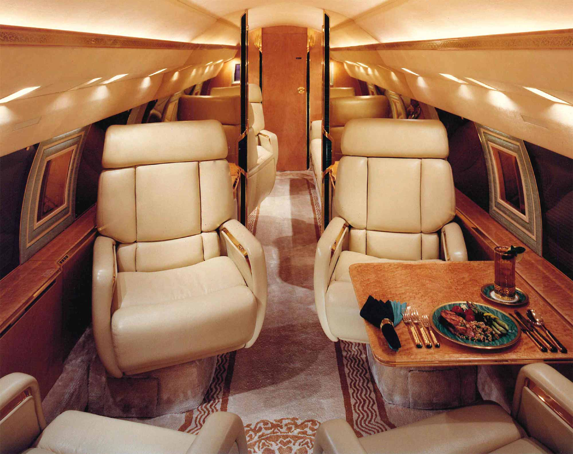 A meal sits atop the passenger table in a custom Gulfstream jet airplane