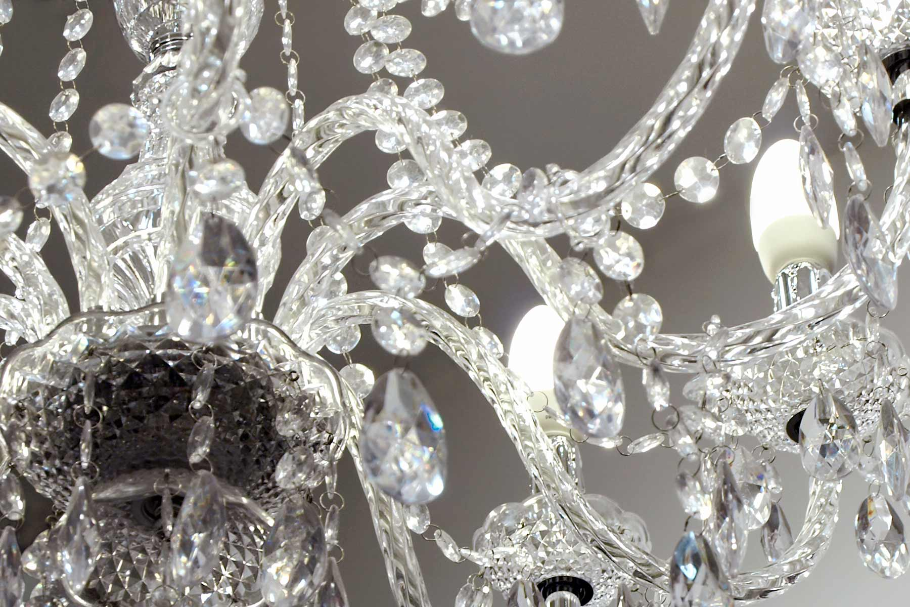A crystal chandelier splashes light across a wall and ceiling