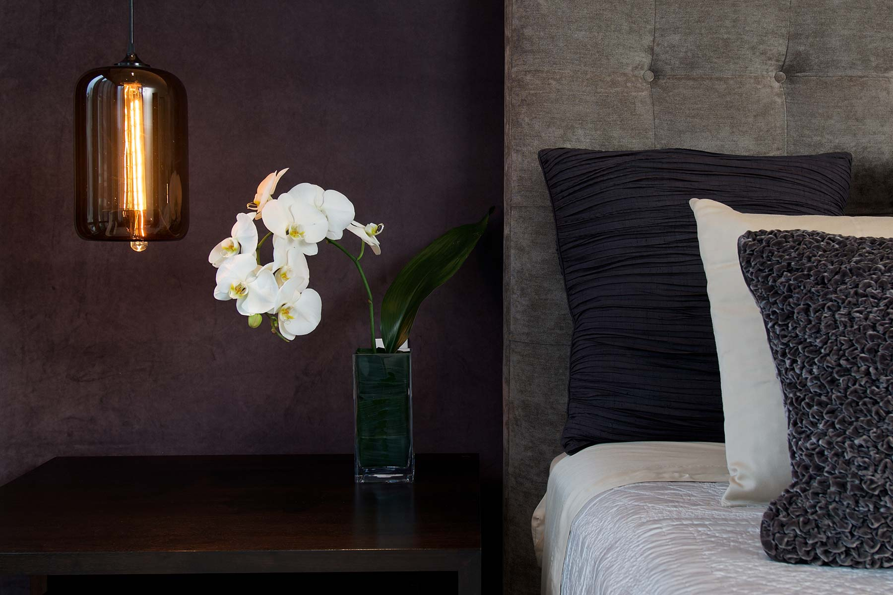 Delicate orchids sit bedside in a luxury destination home