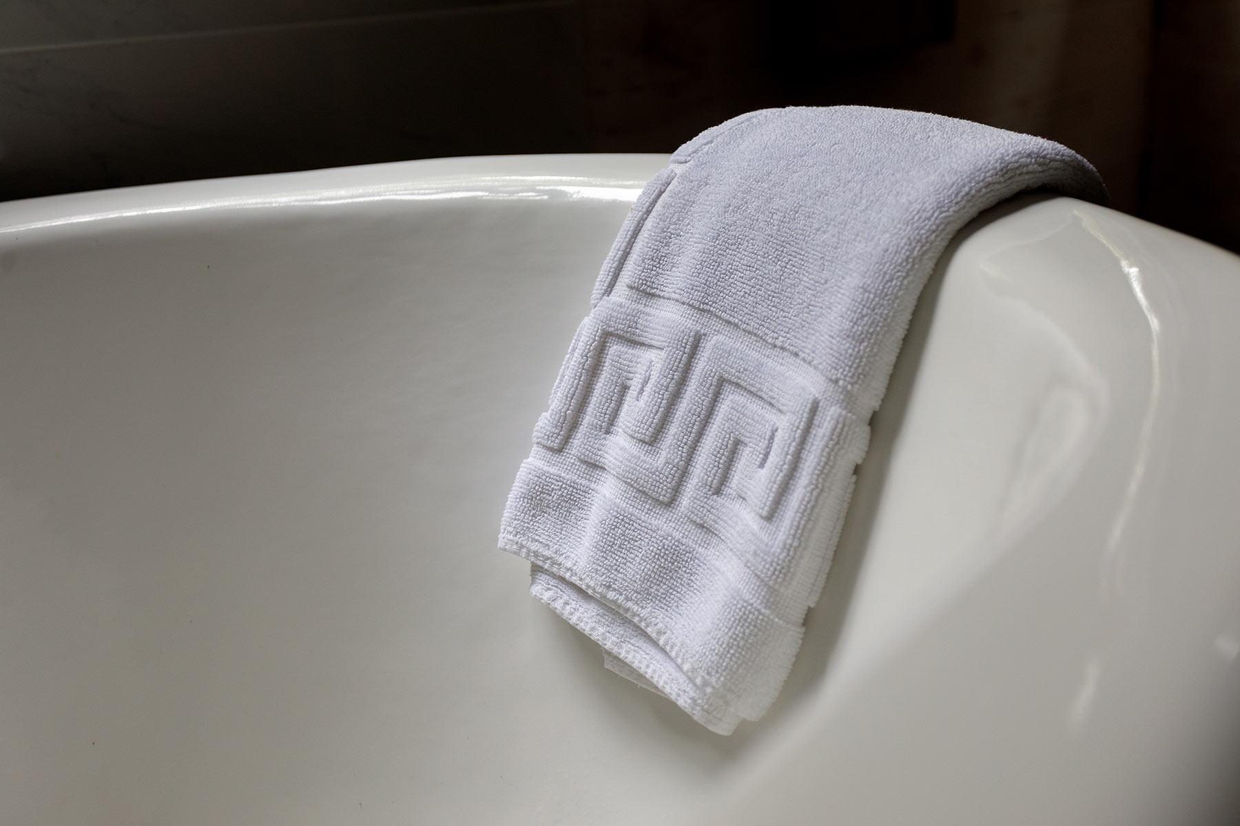 A rich bath mat folded over a vintage claw-foot bathtub