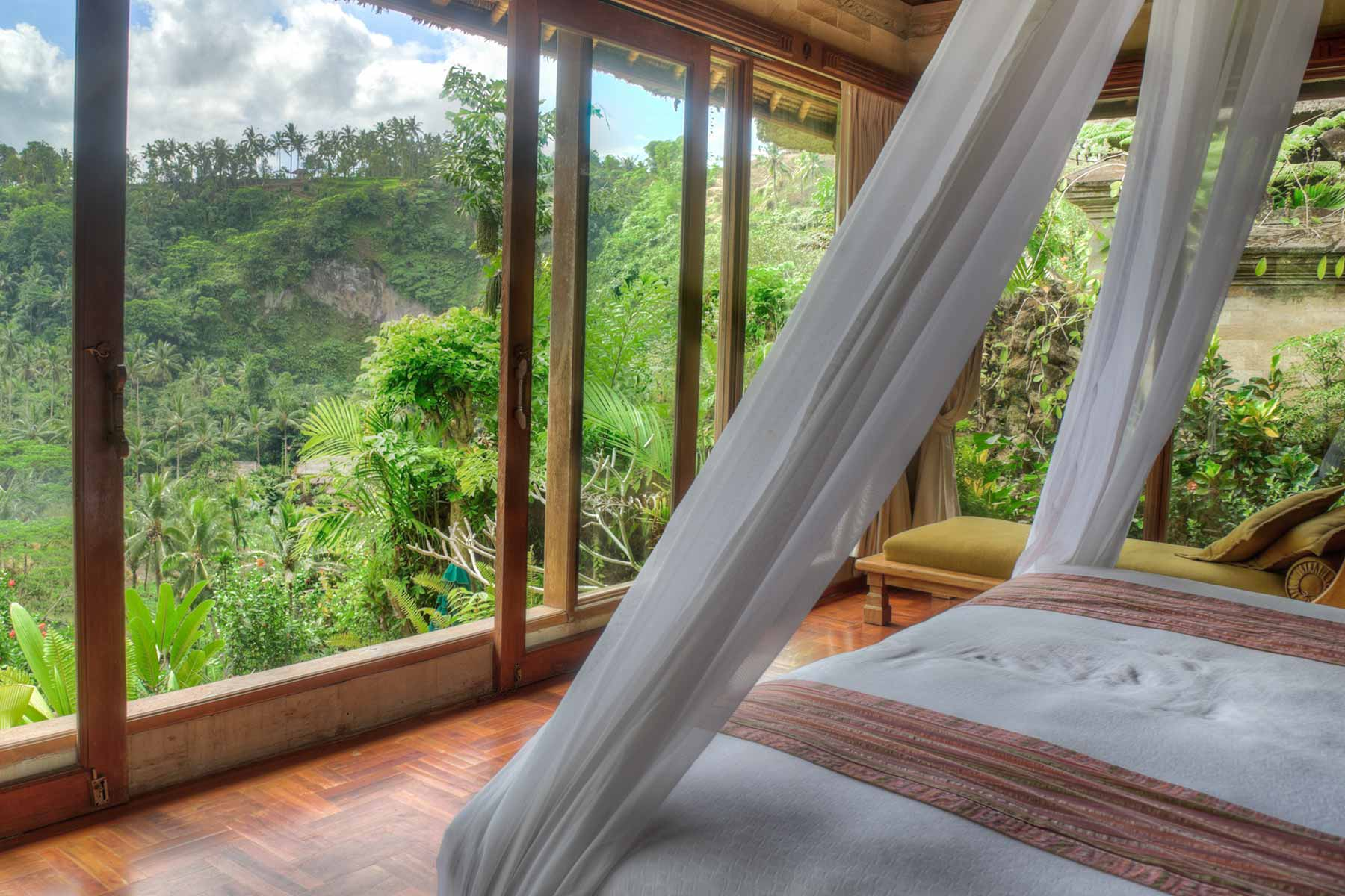 Linens adorn a destination club home master bed surrounded by jungle