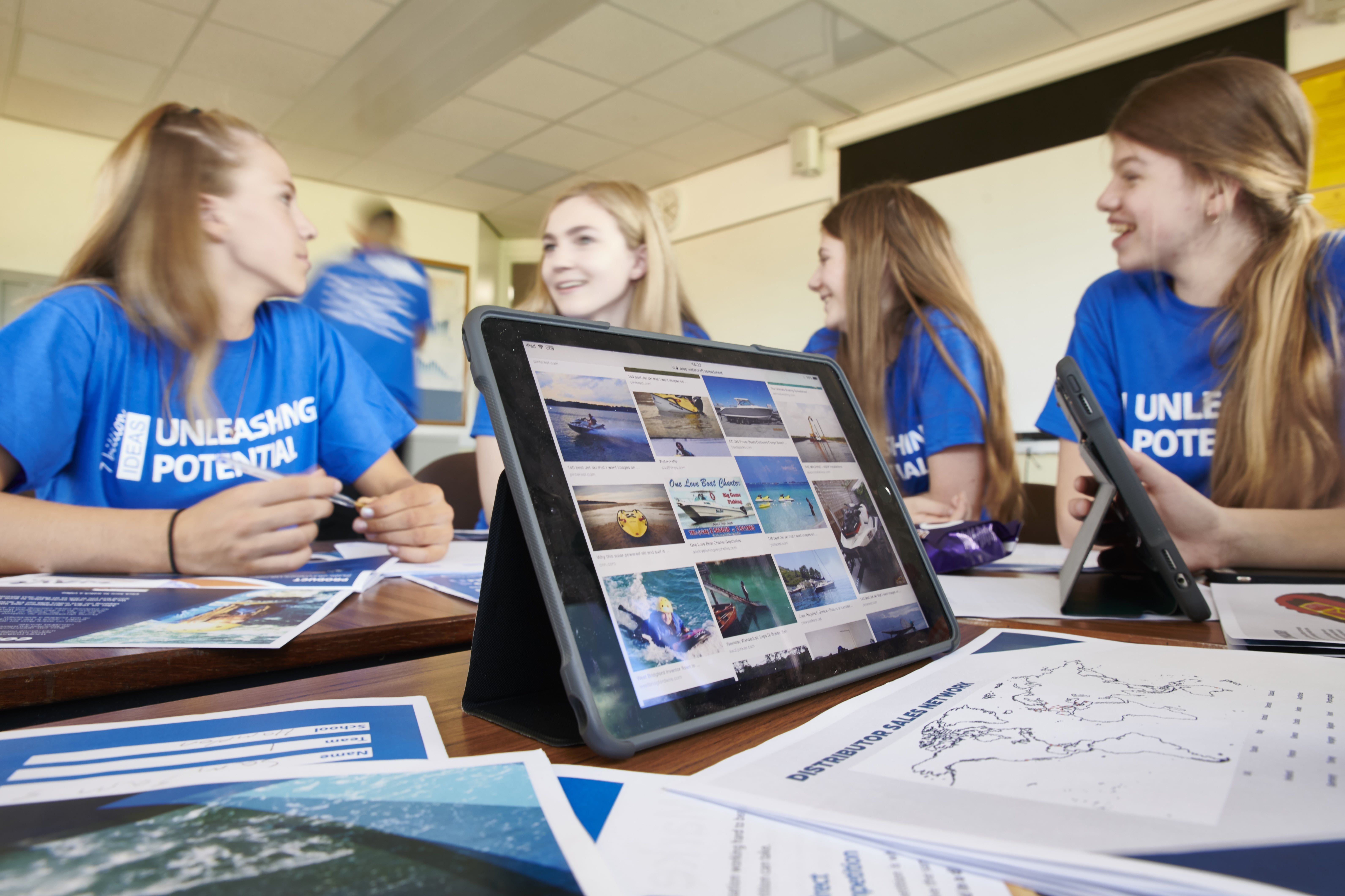 Students on Unleashing Potential gather round a tablet