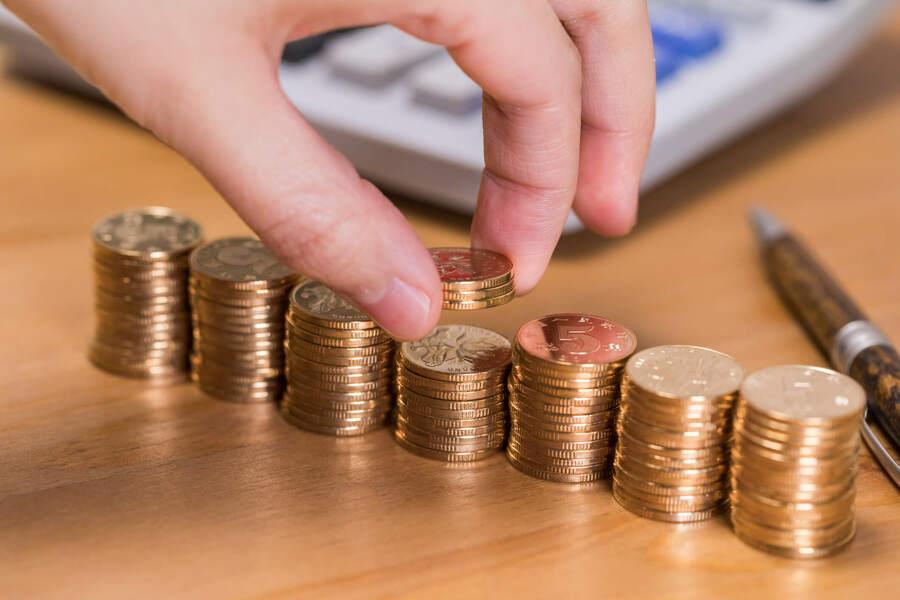 mão empilhando dinheiro remetendo a ideia de salario complessivo