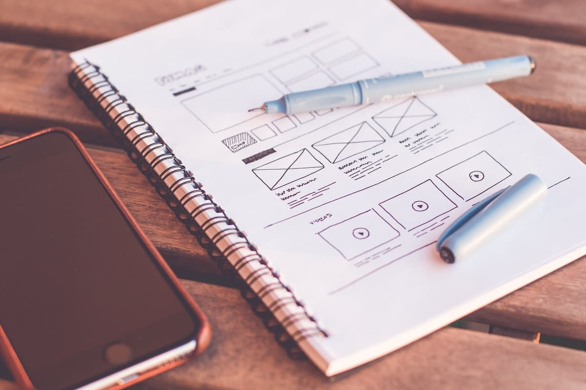 wireframe drawing on notebook with pen on top and phone to the side