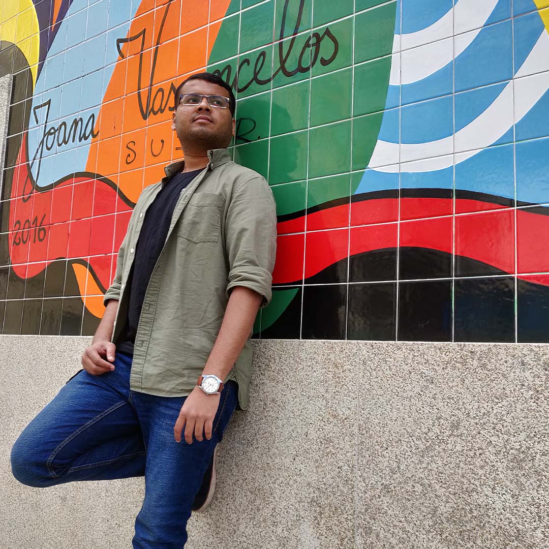 Abhishek in front of a graffiti wall