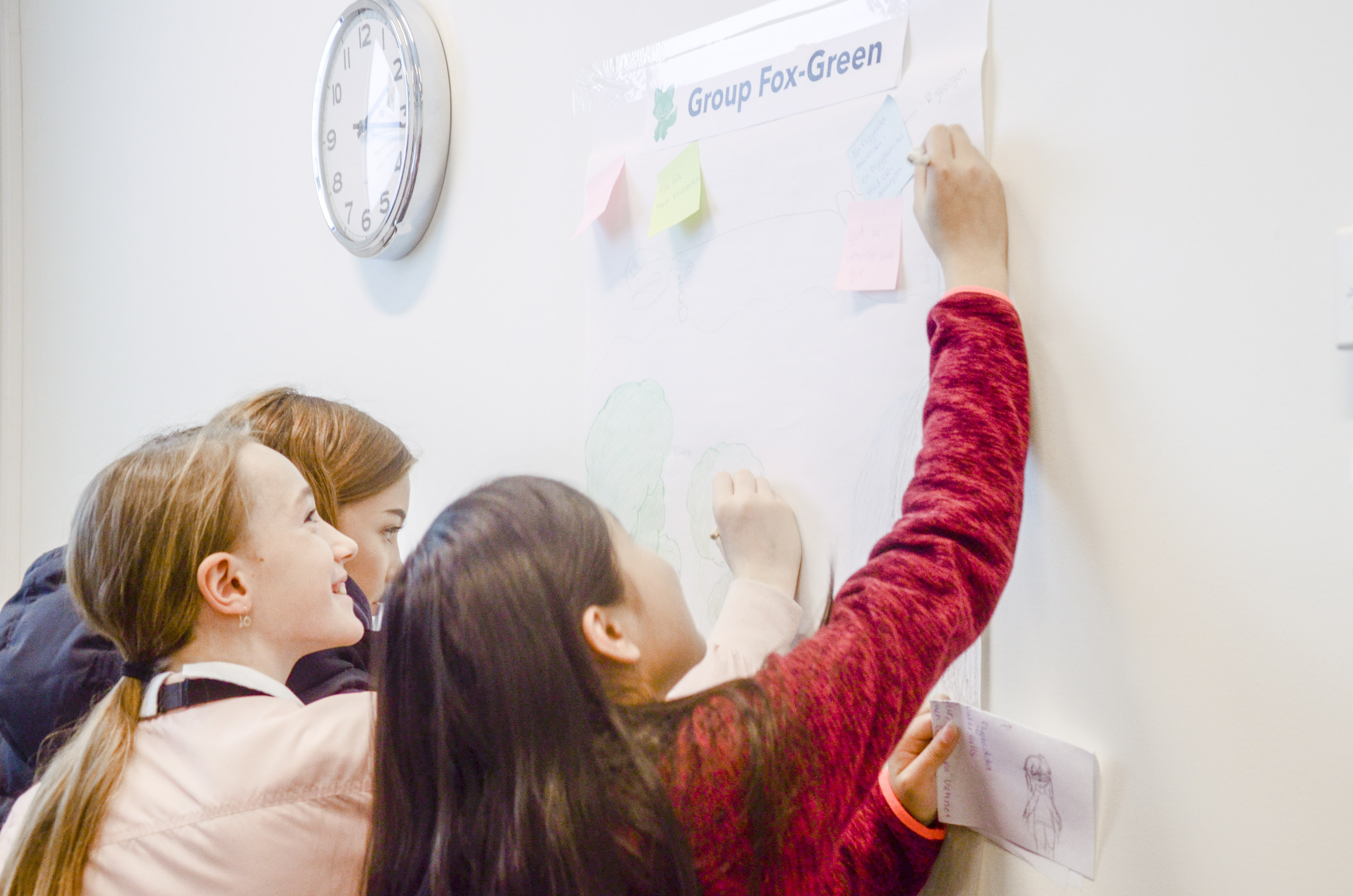 Group of Girls drawing a poster presenting their ideas