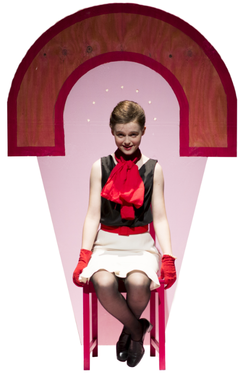 A woman sits on a red chair in front of a pink and red stylized shape. She wears red gloves and a big red bow, and has a sly smile on her face.