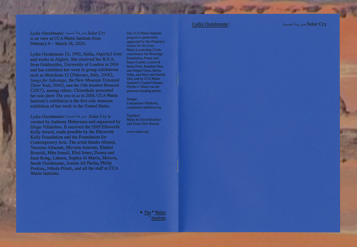 A deep cobalt blue cover of a exhibition catalog is splayed open, showing Bothe the front and back cover. The  cover has the name of the artist: Lydia Ourahmane, and the title of the exhibition at The Wattis Institute, Solar Cry, both in English, and in Arabic.