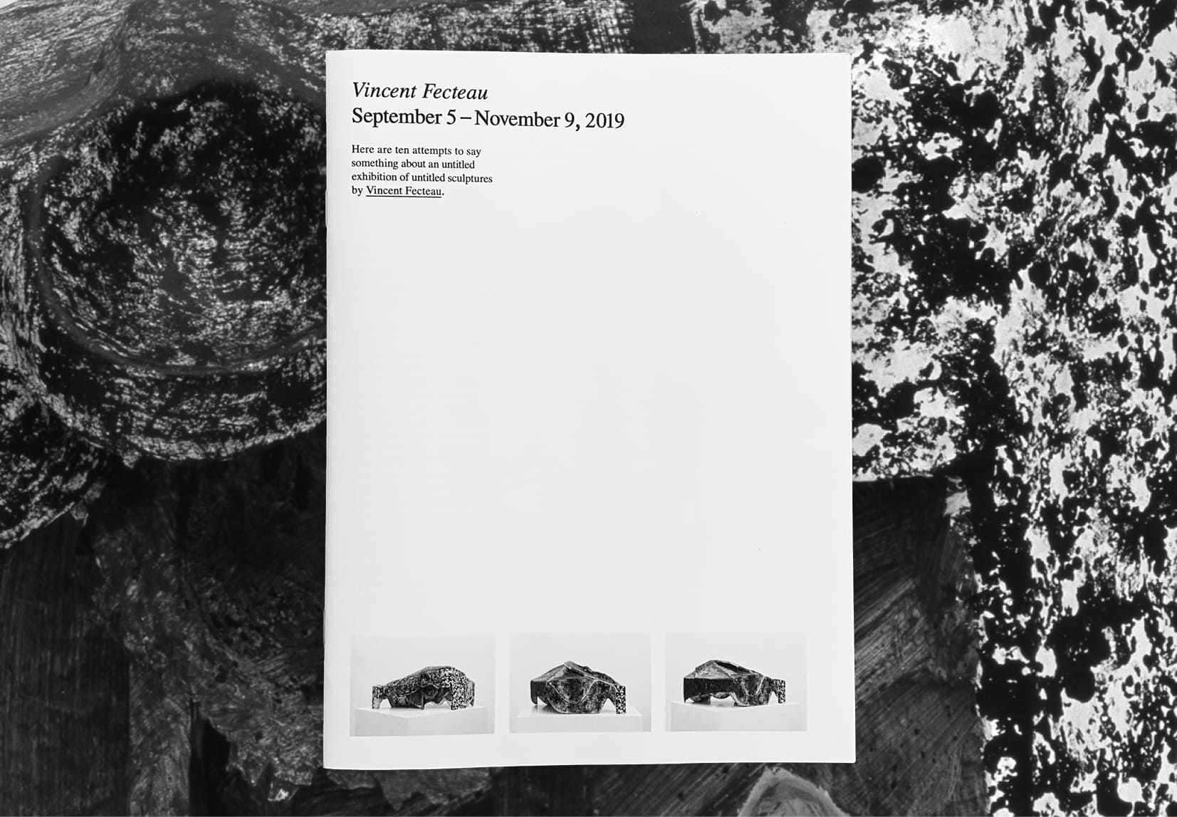 A white exhibition catalog cover floats over an abstract black and white image. The catalog has the artists name on it, Vincent Fecteau, along with three images of the same sculpture from three different perspectives along the bottom. The exhibition took place at The Wattis Institute.
