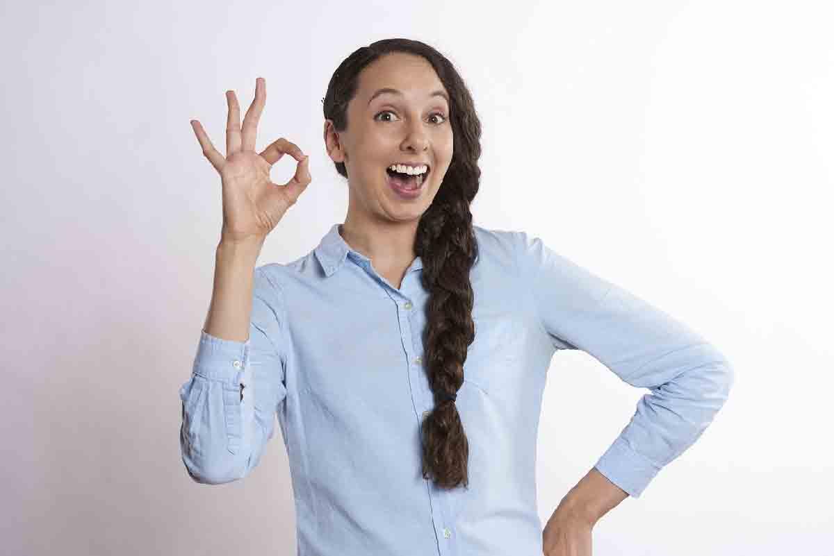 una donna sorride facendo il cenno dell'ok