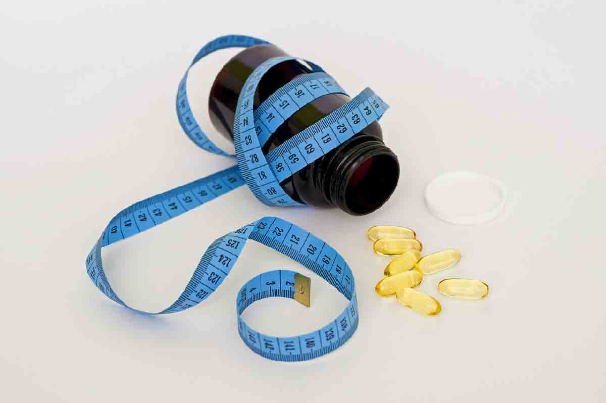 un flacone di pillole di integratori con un nastro azzurro