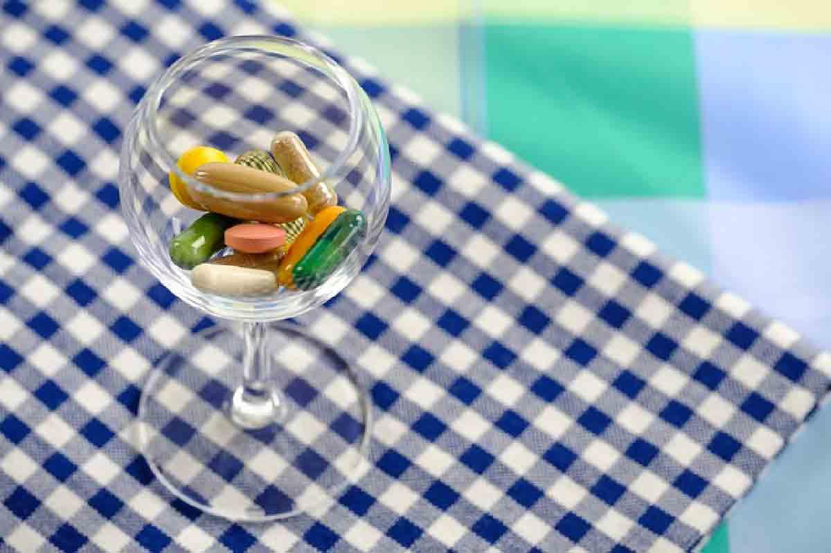 delle pillole di integratori riprese in un bicchiere
