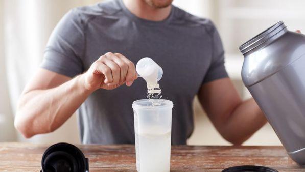 un uomo versa delle proteine in polvere nel suo bicchiere