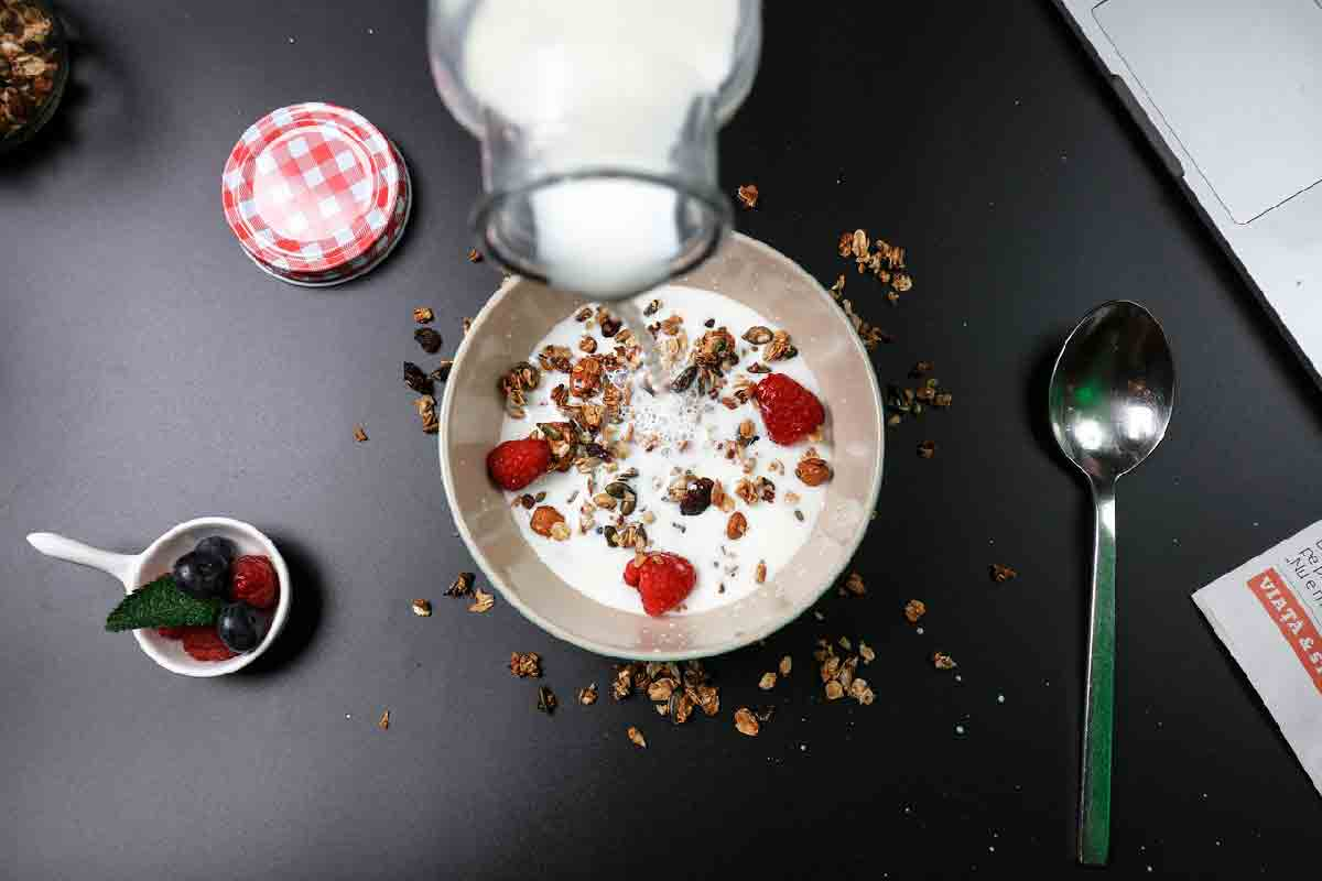 una tazza di cereali viene ripresa mentre viene riempita di latte